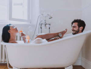 Couple taking bath together blowing bubbles