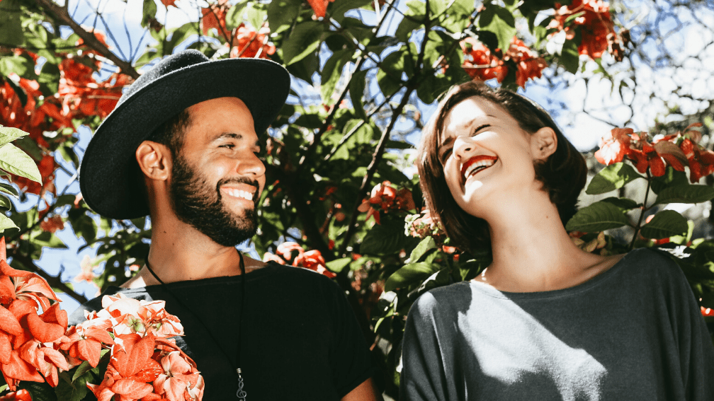 Couple laughing together with background of trees and flowers